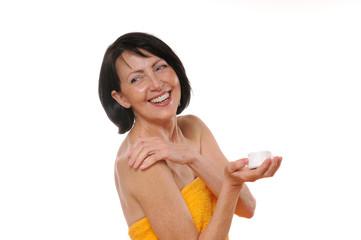 portrait of happy senior woman using body lotion
