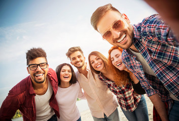 Group of young people having fun outdoors on the beach  Wall mural