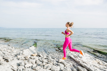 Young attractive fitness girl running on stones beach