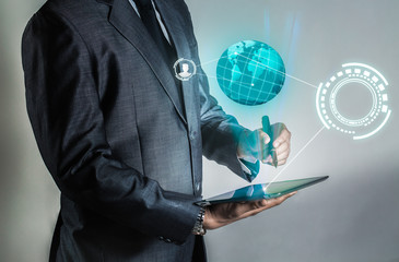Businessman is holding tablet and open hologram to connect people with black space for your icon, internet of things background and high technology business background.