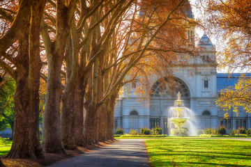 A row of trees leading to a fountain in front of the Royal Exhibition building at Carlton Gardens in Melbourne, Australia.