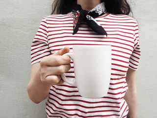 White mug mockup. Close up of a young woman wearing a striped t-shirt and scarf and holding cup of tea or coffee. Feminine stock photography. Front view.
