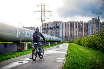 Casual young man riding his bicycle along the gas pipe in the city after rain