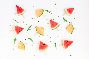 Watermelon popsicle and melon popsicle on white background. Top view, flat lay