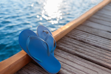 Blue flip flops on the wooden pier with blurred sun glare on the sea on the background
