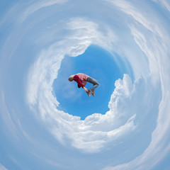 Photo manipulation with spherical panorama of a man free falling between clouds..