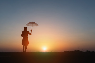 Silhouette of woman with umbrella on sunset background