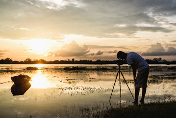 Photographer standing in front of boat during capturing landscape sunset moment at fisherman village