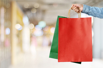 Hand holding red shopping bag on blur store background, banner with copy space for text, template, business concept