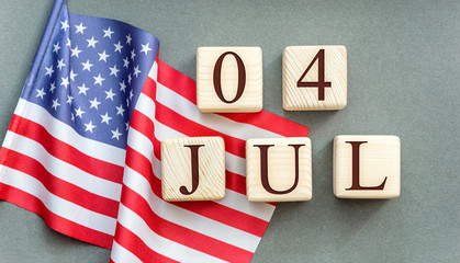 Wooden cubes with date of 4 july and american flag on grey background.