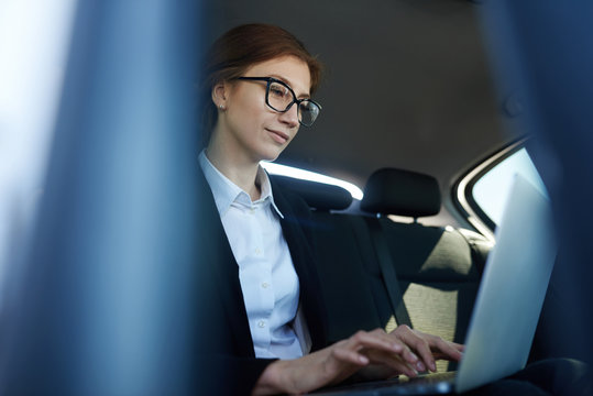 Mid-age business woman working while being in the car