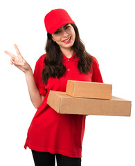 Young delivery woman making victory gesture