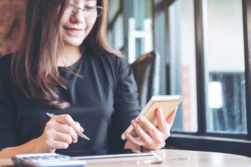 A beautiful Asian business woman working , holding notebook and using calculator in office
