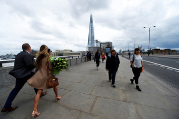 A woman carries a bunch of flowers across London Bridge, in London
