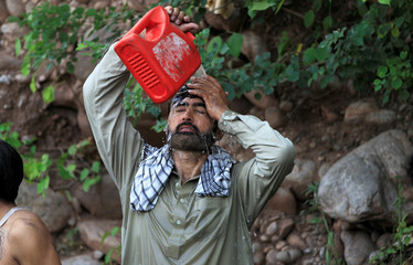 A man pours on himself water leaking from a broken pipe to cool off during a heatwave in Islamabad