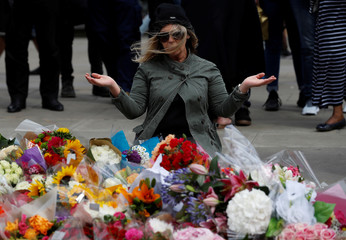A woman sits in front of floral tributes on the south side of London Bridge near Borough Market after an attack left 7 people dead and dozens of injured in London