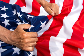 Elderly man hands holding a USA flag. The concept of caring for pensioners.