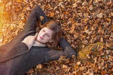 Beautiful Woman lying on Autumn leaves and dreaming
