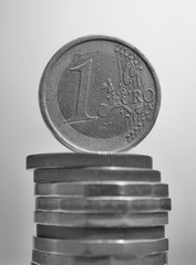 Side view of tall pile of metal coins in golden and copper color in front of silver background with one Euro (European currency EUR) coin on the top