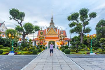 Traveler selfie and take a photo two statue giant at churches Wat Arun, Bangkok, Thailand