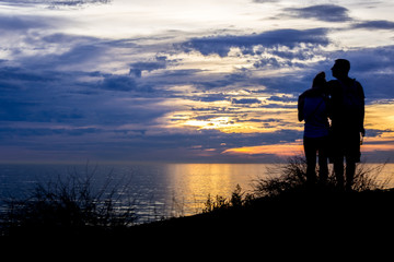 Romantic couple watching a sunset on the cliffs at Pelican Cover