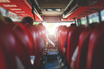 View from back seat in a bus. People sitting in a coach. Public transportation concept with summer vibe.