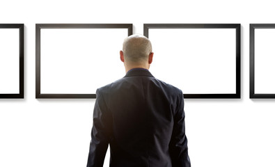 Business man watching blank photo frame on white wall art gallery, art exhibition