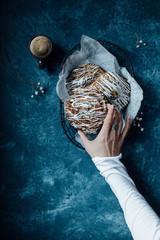 Right hand holding cinnamon bun, blue background