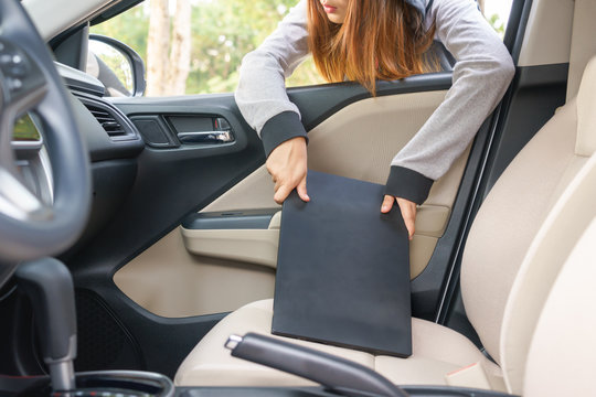 Woman burglar steal a laptop through the window of car - theft concept.