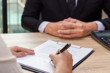 Woman signing contract or loan agreement document with businessman waiting for.