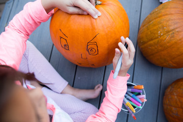 Overhead view of child drawing on pumpkin