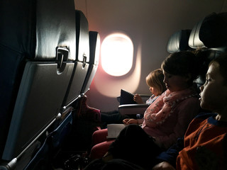 Aeroplane interior view of three seated children
