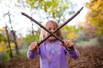 Young girl in woods holding two sticks in a cross shape