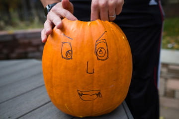 Halloween, carving out a pumpkin with a face drawn on.
