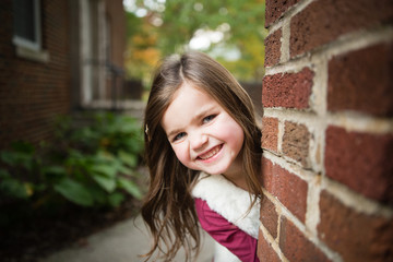 Young girl  looking round brick wall, smiling