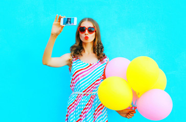 Pretty woman taking a picture on a smartphone with an air colorful balloons on a blue background