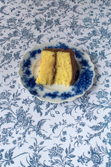 Chocolate icing on yellow cake slice on blue flower background