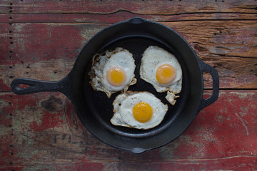 Three sunny side up fried eggs in cast iron pan on wooden table