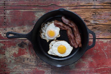 Two sunny side up fried eggs with two strips of baccon in cast iron pan on wooden table