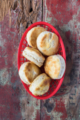 Country biscuits in red basket on rustic painted table in top down view