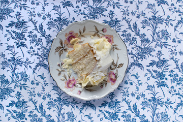Vanilla cake slice on fine china plate sitting on blue flower background