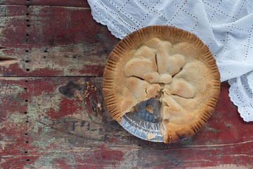 handmade apple pie on rustic table with white linen