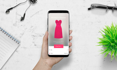 Woman shopping with smart phone. Pink woman dress on ecommerce app. White desk in background. Plan, glasses, headset beside.