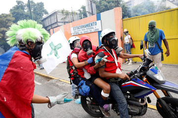 An injured demonstrator is helped by volunteer members of a primary care response team during a rally against Venezuela's President Maduro in Caracas