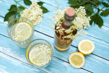 Two glasses of elderflower lemonade and bottle, top view