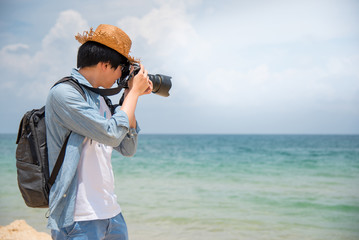 young Asian man photographer with jean shirt and hat take photo of tropical island beach and turquoise sea, seascape background for summer holiday and vacation travel concepts