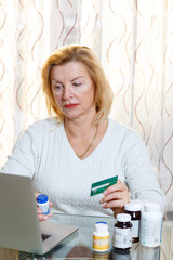 Old Senior woman researching and buying prescription medicines online using credit card