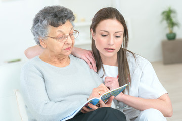Elderly lady reading a magazine, younger woman by her side