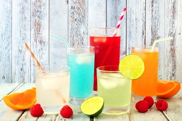 Group of cool colorful summer drinks against a rustic wood background