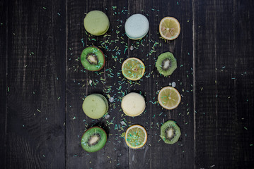 Green and white macaroons with kiwi, orange and lemon in order on a wood gark table